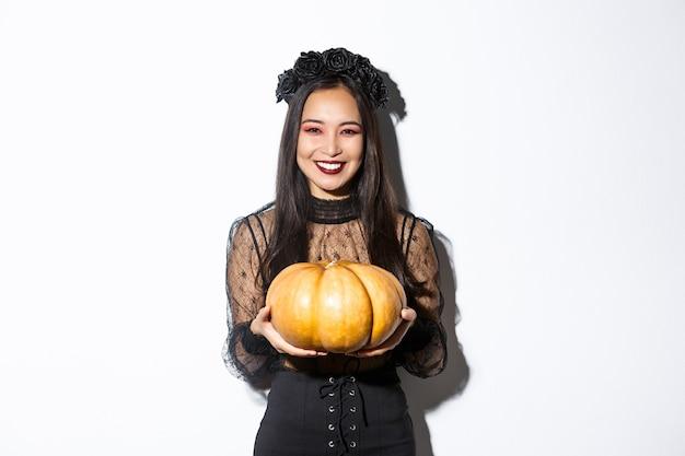 Glückliche schöne frau im schwarzen spitzenkleid, das halloween-feiertag genießt, in die kamera lächelt und kürbis hält, der über weißem hintergrund steht.
