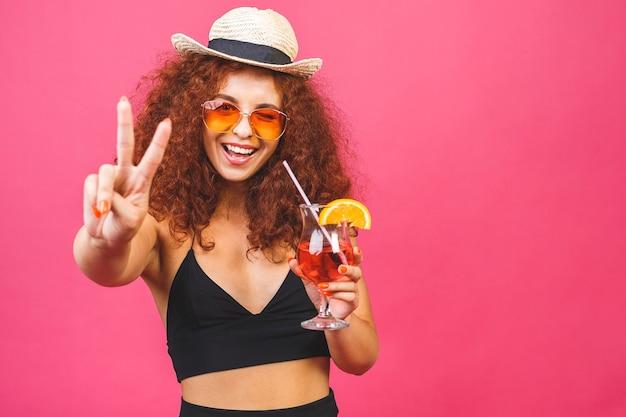 Glückliche schöne frau im sommer lässige kleidung mit einem glas cocktail trinken studio schuss isoliert