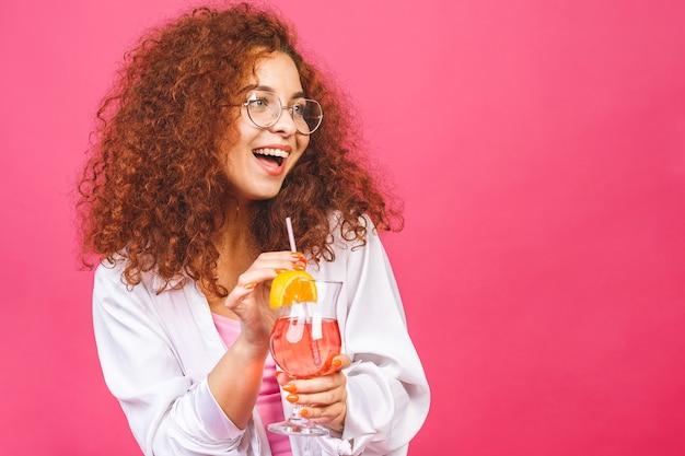 Glückliche schöne frau im sommer lässige kleidung mit einem glas cocktailgetränk