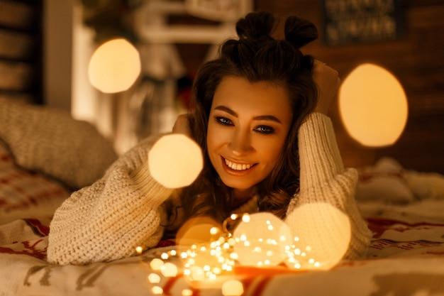 Glückliche schöne frau im vintage-strickpullover mit festlichen lichtern auf dem bett