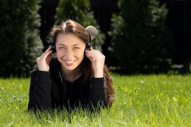 Glückliche schöne frau in den kopfhörern, die auf gras draußen liegen und musik hören