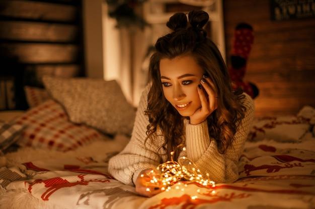 Glückliche schöne frau in einem weinlesepullover mit feiertagslichtern, die auf einem bett am vorabend von weihnachten träumen