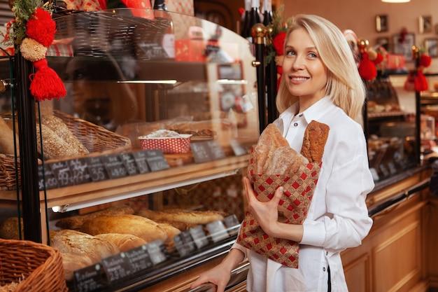 Glückliche schöne frau lächelnd, träumerisch weg suchend beim einkaufen für brot bei lokaler bäckerei