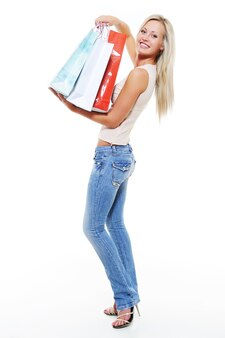 Glückliche schöne frau mit taschen nach dem einkaufen - porträt in voller länge