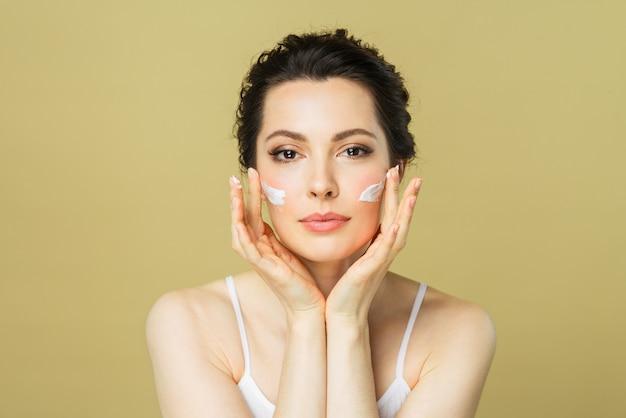 Glückliche schöne frau trägt creme auf ihr gesicht kosmetik schönheit und spa auf