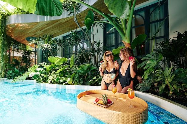 Glückliche schöne freundinnen, die am rand des swimmingpools sitzen, lachen und frisches obst essen