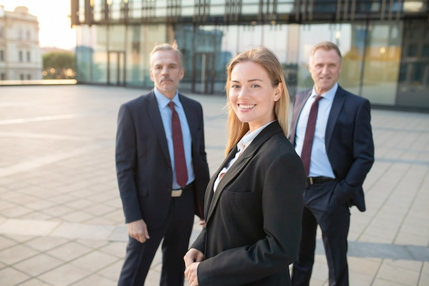 Glückliche schöne geschäftsfrau, die büroanzug trägt, draußen steht und kamera betrachtet. männliche geschäftskollegen stehen dahinter. business-team-konzept