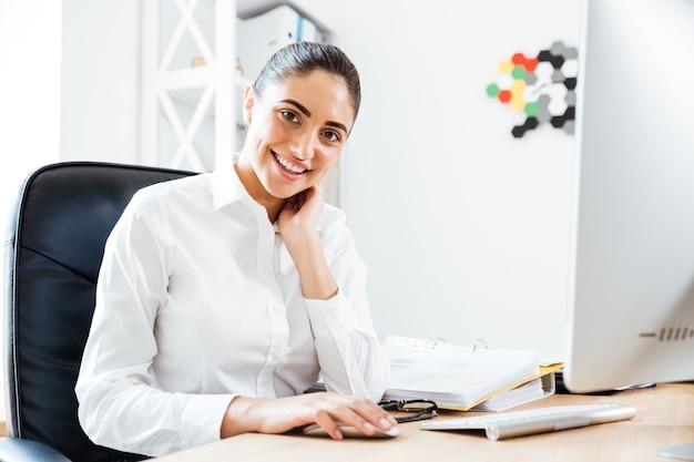 Glückliche schöne geschäftsfrau, die laptop für die arbeit verwendet, während sie im büro sitzt