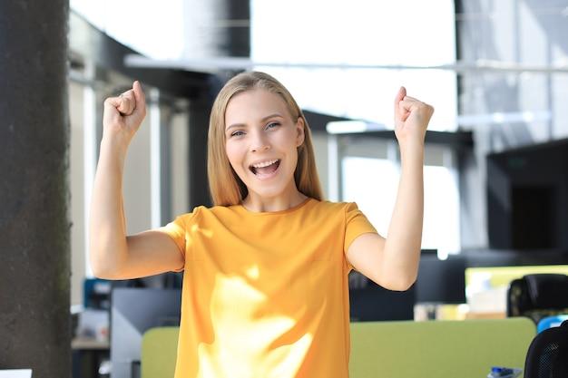 Glückliche schöne geschäftsfrau mit erhobenen armen und blick in die kamera, während sie im büro steht.