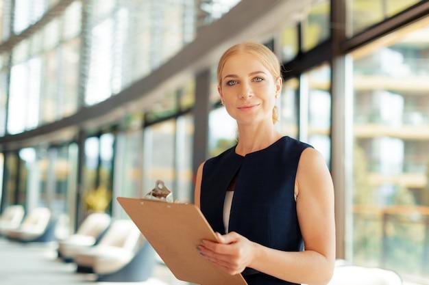 Glückliche schöne geschäftsfrau mit klemmbrett im büro.