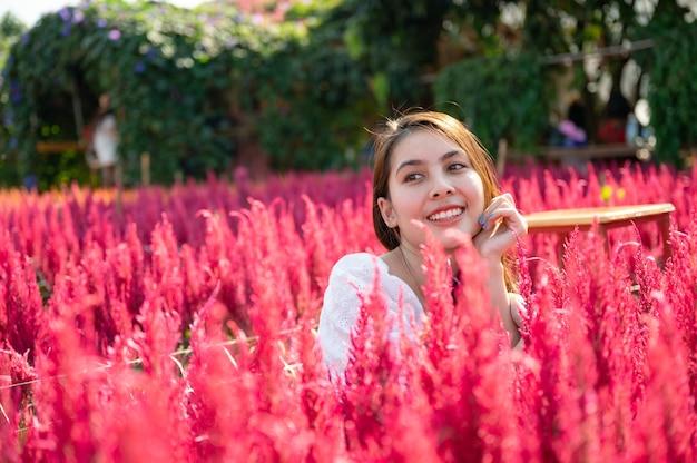 Glückliche schöne junge asiatische frau, die im hahnenkamm-blumengarten sitzt