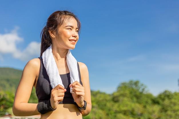 Glückliche schöne junge asiatische frau, die mit schweiß auf ihrem gesicht nach ihrem morgenübungslauf lächelt
