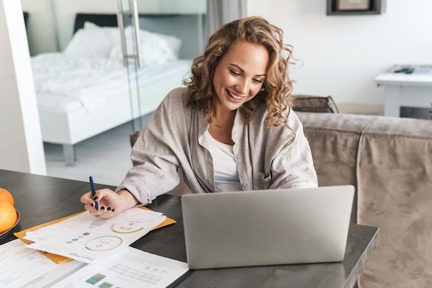 Glückliche schöne junge blonde frau, die zu hause am tisch sitzt, am laptop arbeitet und notizen macht