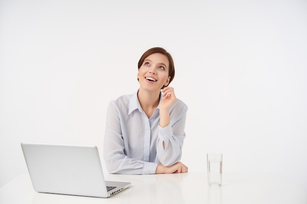 Glückliche schöne junge braunhaarige frau mit natürlichem make-up, das fröhlich nach oben schaut und hand erhoben hält, am tisch auf weiß mit laptop und glas wasser sitzend