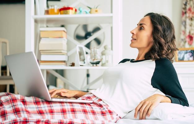 Glückliche schöne junge brünette frau arbeitet mit ihrem laptop, während sie zu hause im bett lag. das freiberufliche mädchen surft im internet