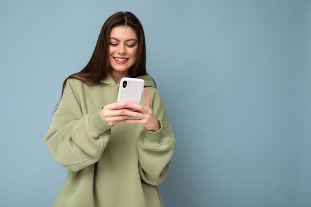 Glückliche schöne junge brünette frau, die einen stilvollen grünen hoodie mit handy-schreiben von sms trägt