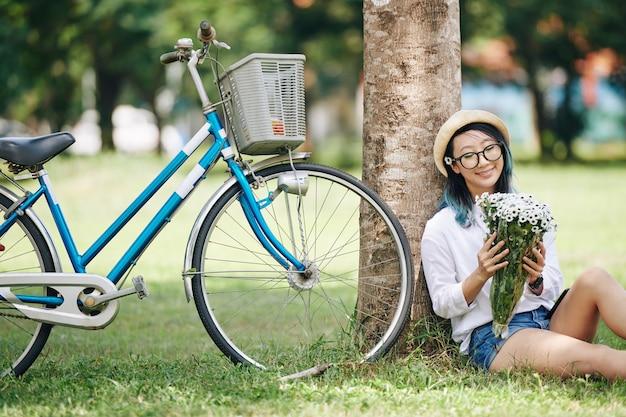 Glückliche schöne junge chinesische frau, die unter dem baum neben ihrem fahrrad sitzt und strauß der weißen blumen in ihren händen betrachtet
