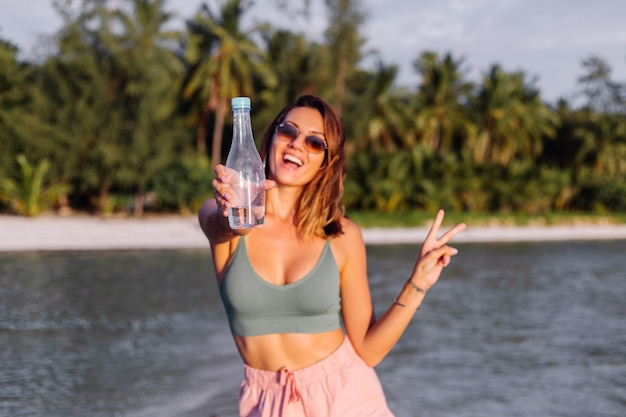 Glückliche schöne junge europäische frau mit plastikflasche wasser in ihrer hand im strand