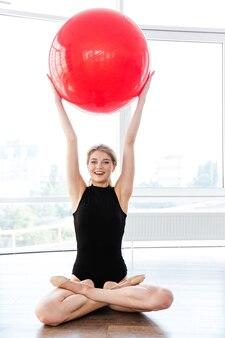 Glückliche schöne junge fitnessfrau im trikot, die mit gekreuzten beinen sitzt und roten fitball hält