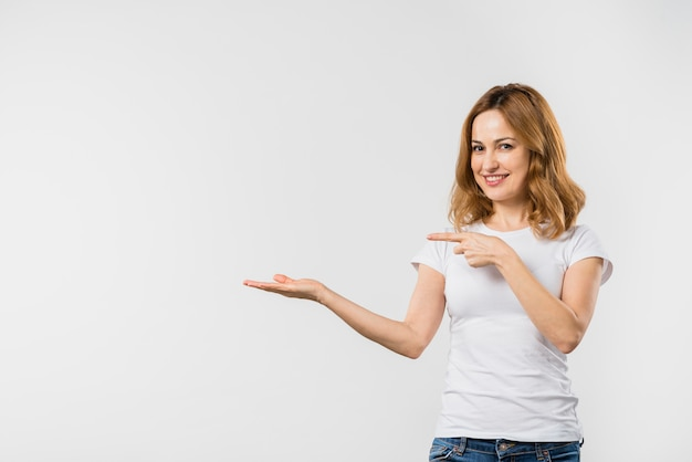 Glückliche schöne junge frau, die an hand auf etwas zeigt