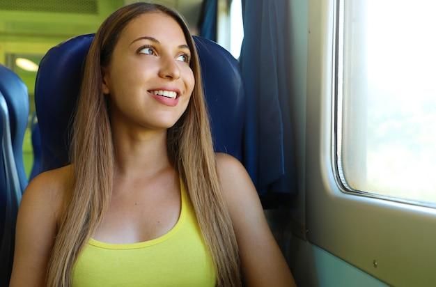 Glückliche schöne junge frau, die durch das zug- oder busfenster schaut. lächelnder hübscher zugpassagier, der auf einem sitz sitzt und durch das fenster schaut.