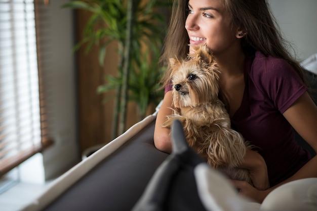 Glückliche schöne junge frau, die fenster mit ihrem hund betrachtet