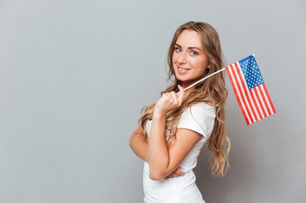 Glückliche schöne junge frau, die flagge der vereinigten staaten von amerika steht und hält