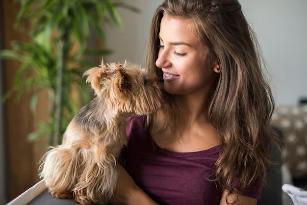 Glückliche schöne junge frau, die mit ihrem kleinen hund aufwirft