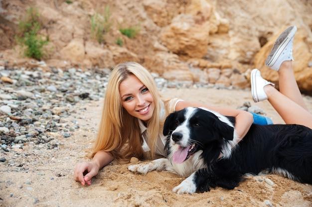 Glückliche schöne junge frau, die sich mit hund am strand entspannt