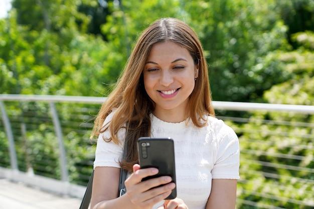 Glückliche schöne junge frau, die textnachricht auf dem handy im freien sendet