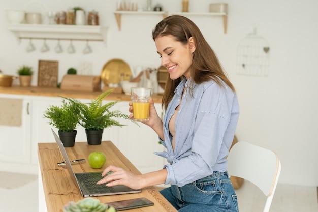 Glückliche schöne junge frau, die zu hause am tisch sitzt, in einem laptop arbeitet und köstlichen orangensaft trinkt. arbeiten und lernen von zu hause aus unter quarantänebedingungen.