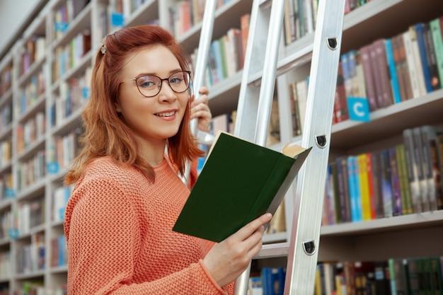 Glückliche schöne junge frau, die zur kamera lächelt, während sie ein buch an der bibliothek liest