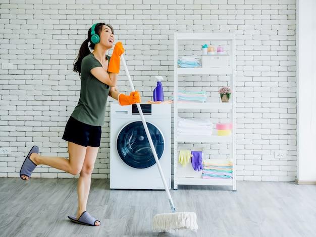 Glückliche schöne junge frau, hausfrau, die gummihandschuhe, pantoffel und grünen kopfhörer trägt, der spaß mit mopp wie ein mikrofon singt, während boden nahe waschmaschine auf weißer wand reinigt.