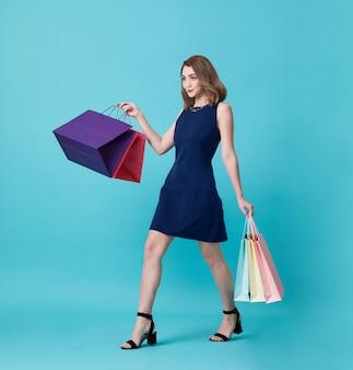 Glückliche schöne junge frau im blauen kleid und in der hand, die einkaufstasche lokalisiert über blauem hintergrund hält.