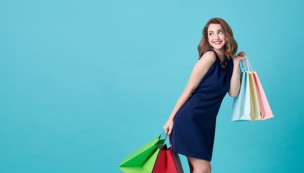 Glückliche schöne junge frau im blauen kleid und in der hand, die einkaufstaschen hält und auf hellblau mit kopienraum betrachtet.