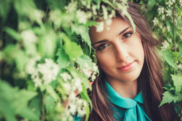 Glückliche schöne junge frau im frühlingsblütenpark. hübsches mädchen mit frühlingsblumen. model im freien