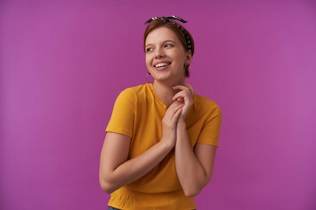 Glückliche schöne junge frau im gelben t-shirt mit dem stirnband auf dem kopf, der lächelt und zur seite im kopierraum über lila wand schaut