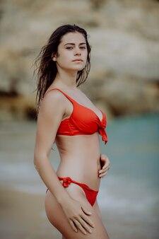 Glückliche schöne junge frau im roten bikini und in der sonnenbrille, die auf dem strandmeer aufwerfen