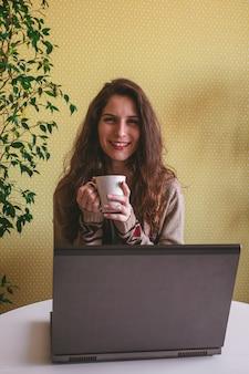 Glückliche schöne junge frau in der freizeitkleidung, die an einem laptop in der küche arbeitet