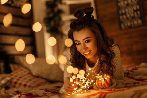 Glückliche schöne junge frau mit einem lächeln in einem vintage-strickpullover mit weihnachtslichtern auf dem bett