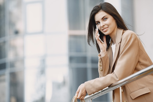 Glückliche schöne junge frau mit einkaufstüten, die auf einem handy eines einkaufszentrums spricht