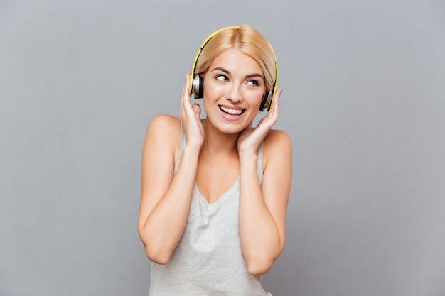 Glückliche schöne junge frau mit kopfhörern, die musik über grauer wand hört