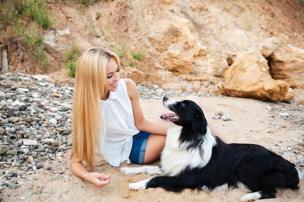 Glückliche schöne junge frau mit süßem hund am strand