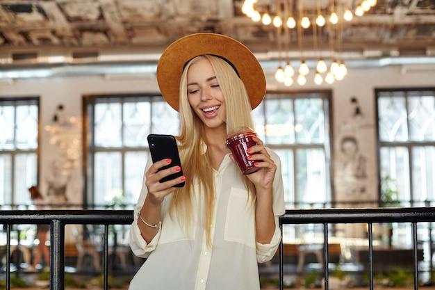 Glückliche schöne junge frau mit telefon in der hand, die bildschirm betrachtet und liebevoll lächelt, smoothie mit stroh trinkend, weißes hemd und braunen hut tragend