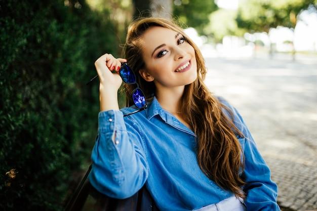 Glückliche schöne junge frau sitzt auf einer bank in einer sommerstraße