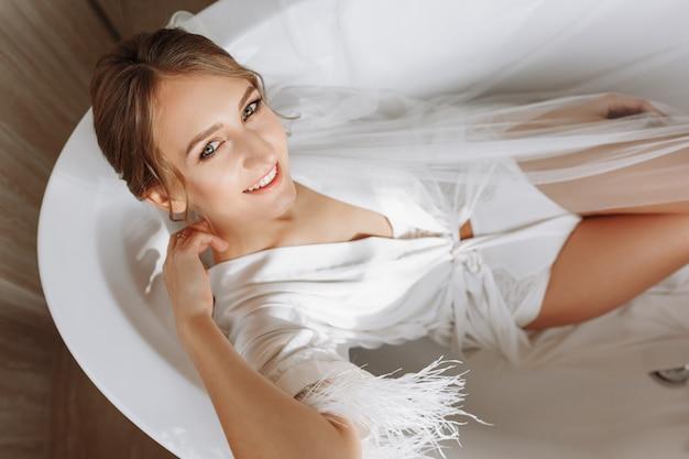 Glückliche schöne junge frau trägt in einem weißen langen schleier, robe und unterwäsche, die im bad auf einem weißen hintergrund sitzen, entspannen.