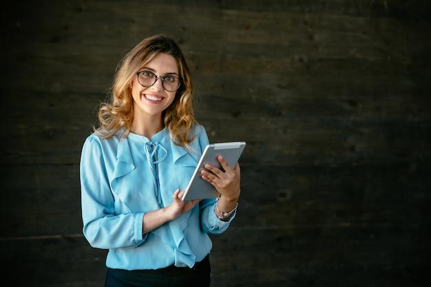 Glückliche schöne junge geschäftsfrau, die mit der tablette, weit lächelnd steht.