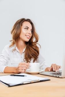 Glückliche schöne junge geschäftsfrau, die mit laptop auf weißem hintergrund sitzt und arbeitet