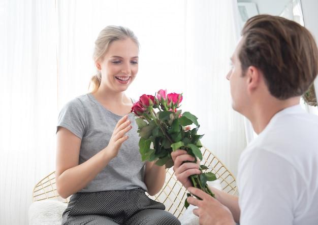 Glückliche schöne junge kaukasische frau bekam strauß rosen mit überraschung vom mann, während auf sofa im schlafzimmer zu hause sitzen.