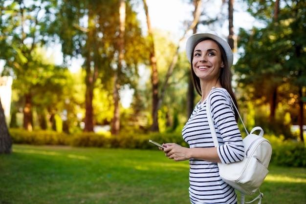 Glückliche schöne junge studentin in einem hut mit smartphone und rucksack, während sie im freien im park geht